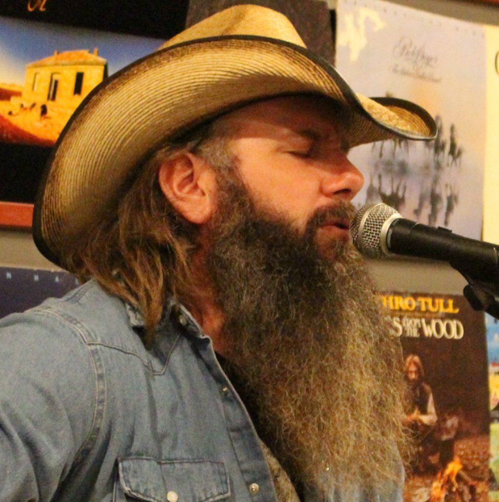 man with long beard wearing straw cowboy hat and jean shirt singing