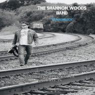 man walking on railroad tracks with guitar